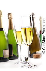 Glasses of champagne with bottles on white