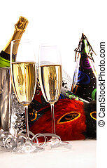 Glasses of champagne with masks and party hats