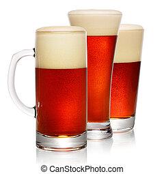 Glasses of dark beer on white