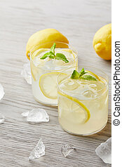 glasses of delicious lemonade with ice and lemons on wooden surface