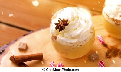 christmas, winter holidays and seasonal drinks concept - glasses of eggnog with whipped cream topping, ingredients, aromatic spices and candy canes on wooden background over snow falling