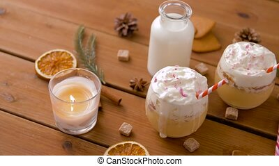 glasses of eggnog, ingredients and spices on wood - ...