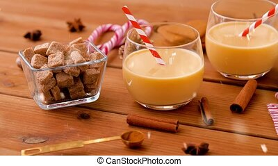 christmas, winter holidays and seasonal drinks concept - glasses with eggnog, brown sugar, aromatic spices and bottle of cream on wooden boards over snow falling