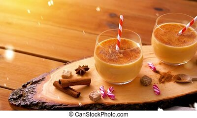 christmas, winter holidays and seasonal drinks concept - glasses with eggnog, ingredients and aromatic spices on wooden board over snow falling