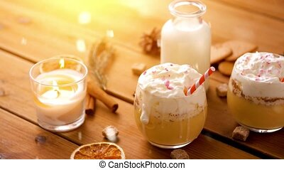 christmas, winter holidays and seasonal drinks concept - glasses of eggnog with whipped cream topping and paper straws, ingredients and candle burning on wooden background over snow falling