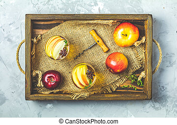 Glasses of homemade organic apple cider with apples in box