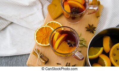 glasses of hot mulled wine with orange and spices -...
