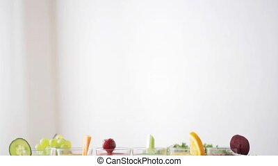 healthy eating, vegetarian food, diet and detox concept - glasses of different juice, vegetables and fruits on table