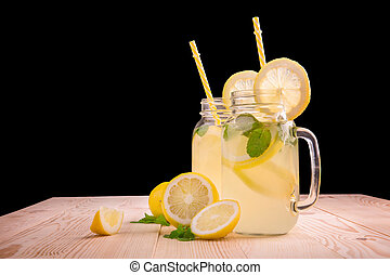 Glasses of lemonade with yellow plastic straws with fresh mint leaves and bright green limes, juicy lemons, and mineral water on a wooden table, on a black background.