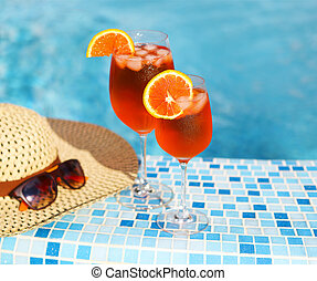Glasses of orange alcohol cocktail on turquiose water...