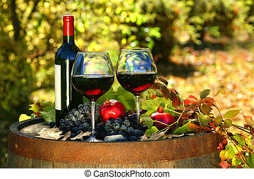 Glasses of red wine on old barrel with autumn leaves