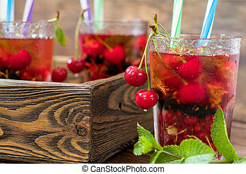 Glasses of refreshing drink flavored with fresh fruit and...