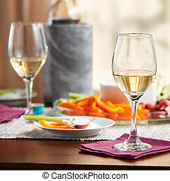 Glasses of white wine on kitchen table with food closeup