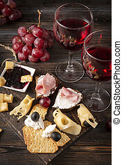 glasses of wine , appetizer, tapas, slices of cheese, cracker, ham, jam, grapes, olives, on a dark wooden background, top view