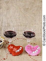 Glasses of wine, two hearts and a basket with chocolate.