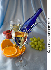 Glasses of wine with oranges and grapes