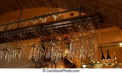 Glasses on a bar hanging upside down. The bar counter in the...