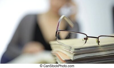 glasses on a pile of exercise books and business woman with...