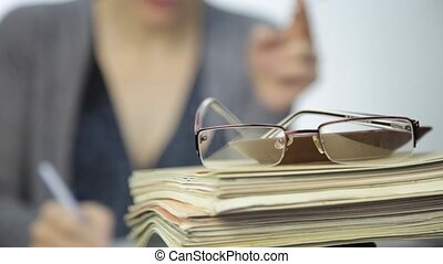 glasses on a stack of exercise books and female teacher with...