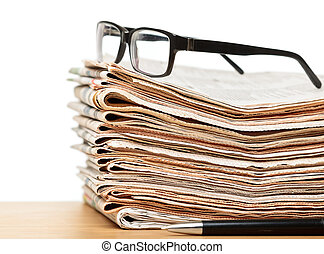 Glasses on a stack of newspapers