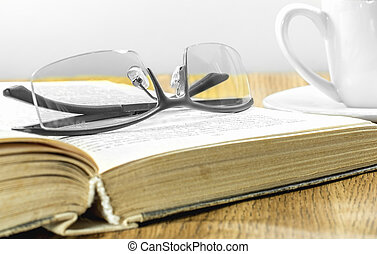 glasses on the book and a cup of coffee