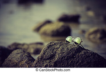 Glasses on the rock near the sea