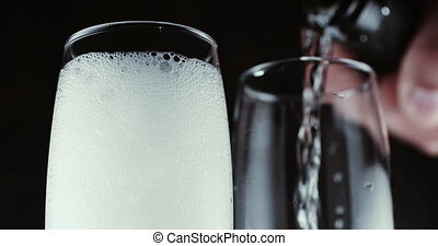 Glasses with champagne bubbles on dark background - Two wine...