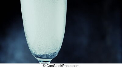 Glasses with champagne bubbles on dark background