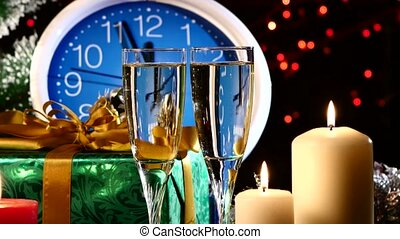 Glasses with champagne on New Year Eve against wall clock, candles, presents, bokeh, garland, on black, cam moves to the left