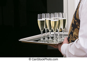 Glasses with champagne on tray in hands of waiter