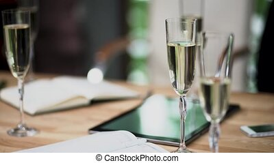 Glasses with champagne stand on the table at a business meeting.