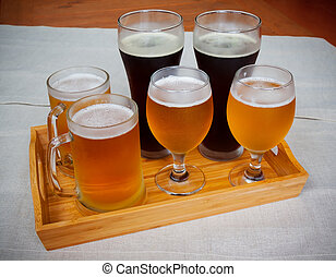 Glasses with different sorts of beer on wooden tray