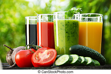 Glasses with fresh vegetable juices in the garden. Detox diet.