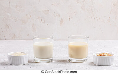 Glasses with healthy rice and oat milk, bowls with rice seeds and oat flakes on white background.