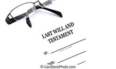 glasses with last will and testament on table -...