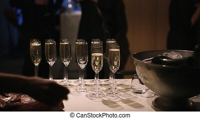 Glasses with sparkling wine at an evening party people in...