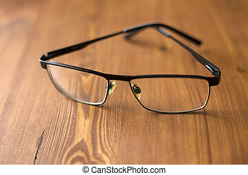 glasses with transparent lenses to improve vision on a wooden background close-up