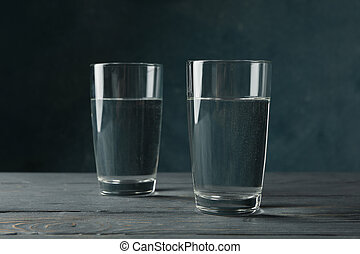 Glasses with water on wooden table, close up
