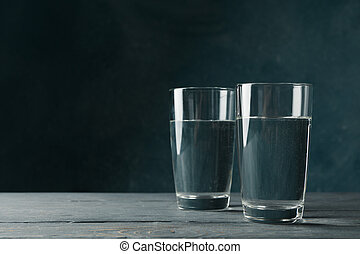 Glasses with water on wooden table, space for text