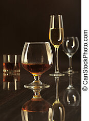 Glasses with white, red wine and cognac or whisky on mirror...