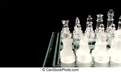 Glassy chess pieces is standing on a chesboard.