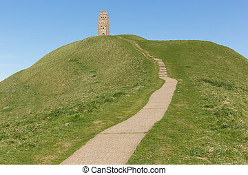 Glastonbury Tor Somerset England, which features the roofless St. Michael's Tower. It is a Scheduled Ancient Monument at the location believed by some to be the Avalon of King Arthur legend