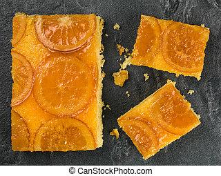 Glazed Candied Orange Sponge Cake on a Black Tile Background