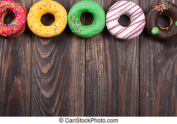 glazed donuts on a black wooden background with copy space for your text. Top view
