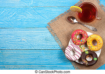 glazed donuts with a cup of tea on a blue wooden background with copy space for your text. Top view