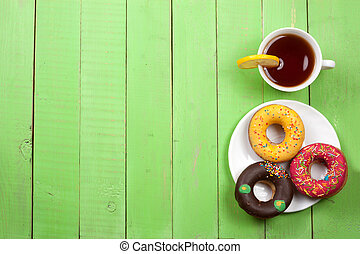 glazed donuts with a cup of tea on a green wooden background with copy space for your text. Top view
