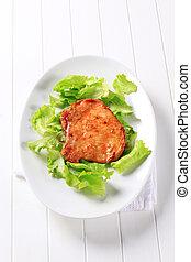 Glazed pork chop on lettuce leaves