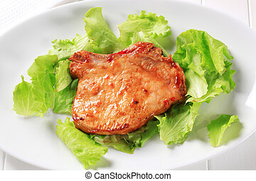 Glazed pork chop on lettuce leaves