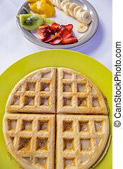 Glazed waffle and fruit slices on colorful plates