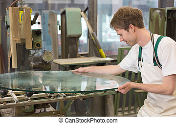 Glazier grinding a pieco of glass - glazier deburrs a glass...